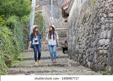 Two young women walking on a cobbled road on an Okinawa trip