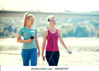Two young women are walking on the beach early in the morning.