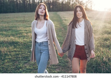 Two young women walking outdoors at sunset. Best friends