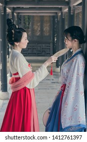 Two young women wearing in Chinese Han clothing in traditional Chinese buildings. Words on their fans are Chinese ancient poems.