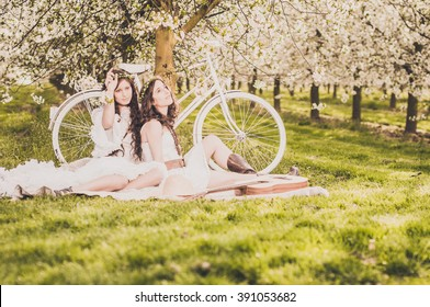Two young women in white dresses sitting relaxed in a meadow between blossoming cherry trees on a ceiling, in the background a white bicycle. In front of them is an acoustic guitar.