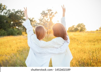 Two young women in white shirts looking on the sunset. Best friends