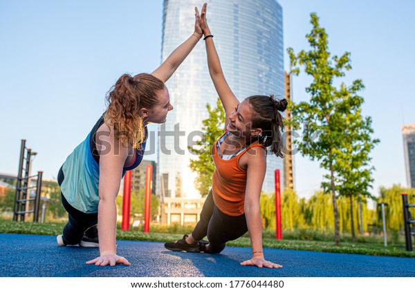 Two young women work out, doing the side table while clapping hands to encourage each other, training in the city in public spaces