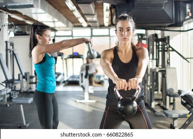 Two young women working out using kettlebells in a cross-training gym.