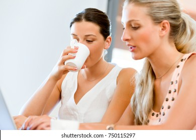 Two young women working together at laptop