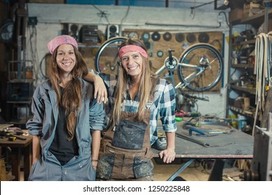 two young women in a workshop posing