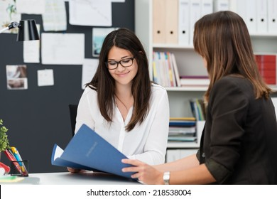 Two young work colleagues discussing some paperwork as they sit together at a desk in the office with focus to a smiling young woman in glasses