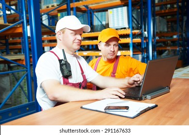 two young workers man in uniform in front of warehouse rack arrangement stillages using notebook laptop computer