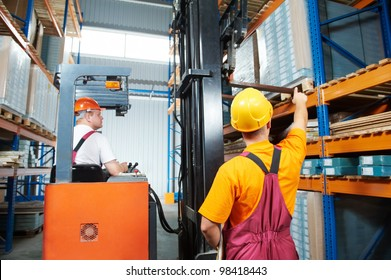 two young workers man in uniform in front of warehouse rack arrangement stillages