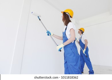Two young workers in uniform painting the wall