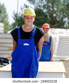 Two young workmen carrying an insulated wooden wall panel on a building site as they move it from the stacked building supplies