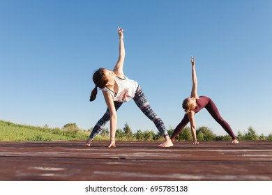 Two Young yoga woman practitioners in group doing yoga on nature at sunny day with blue sky