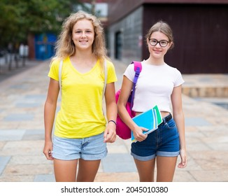 Two youth girls with backbacks going to school together.