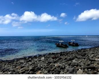 Two Zodiac boats on the shoreline of a rocky beach on Kauai island, Hawaii