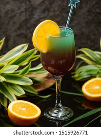Two-colour cocktail in wine glass decorated with orange and stirrer