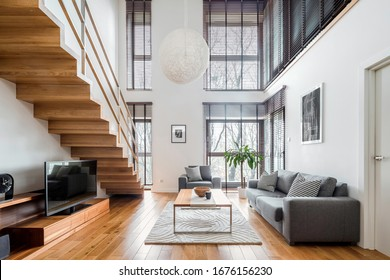 Two-floor apartment with spacious living room with wooden stairs, hardwood floor and many, big windows