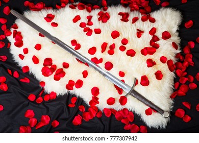 two-handed sword and scarlet rose petals on a white sheepskin