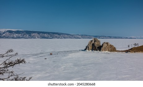 A two-headed granite rock, devoid of vegetation, rises above a frozen lake. A car is visible on the snow-covered ice, tiny silhouettes of people walking. Mountains against the blue sky. Baikal.