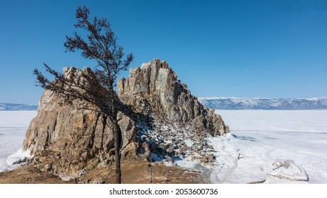 A two-headed granite rock, devoid of vegetation, rises on a frozen snow-covered lake. There are cracks on the stones. Background - blue sky, mountain range. In the foreground is a bare tree. Baikal