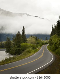A two-lane road winds through the trees in Alaska, with misty clouds and mountains in the background.