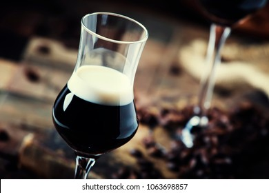 Two-layer cocktail with coffee liqueur, vintage wood background, selective focus