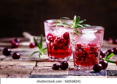 Two-layer cocktail with cranberry vodka, rosemary, soda and ice, vintage wooden background, selective focus