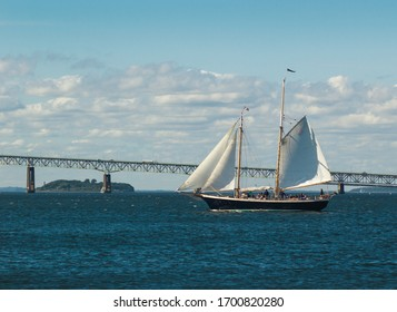 A two-masted sailing ship giving harbor tours with Newport Bridge in the background