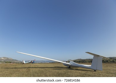 a two-seater white glider is standing on the ground in anticipation of a flight. Clear sky. Autumn.