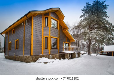 Two-storey cottage made of wood. Cottage in the background of snow. Winter landscape with private house.