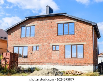 Two-storey house made of red brick. Metal-plastic windows. Newly built house