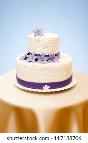 Two-storied white wedding cake with violet marzipan flowers decoration