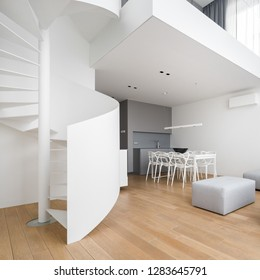Two-story home interior with white, spiral staircase and dining table