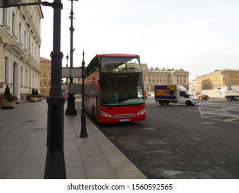 Two-story red bus for city tours parked on the pavement.