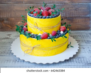 two-tier wedding cake with blueberries and strawberries with eucalyptus
