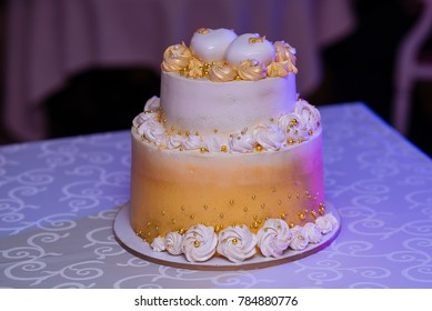 Two-tier white-gold wedding cake with cream and cakes. Candy bar
