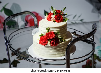 two-tiered appetizing white creamy wedding cake decorated with red and pink roses served on glass tray