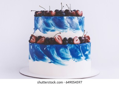 Two-tiered cake with blue brushstroke and fresh berries isolated on white background