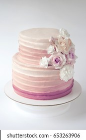 Two-tiered cream wedding cake decorated with flowers from mastic on a white background. Picture for a menu or a confectionery catalog.