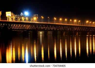 Two-tiered railway bridge across the Dnieper River in Dnipro City at night Dnepropetrovsk, Dnipropetrovsk, Dnepr Ukraine. Lanterns are reflected in water