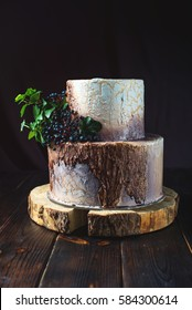 two-tiered wedding cake in the form of stump wood and bark with a twig of wild cherry and green leaves on a dark wooden background.