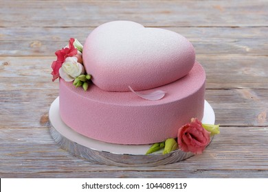 Two-tiered wedding pink cake decorated with heart, edible chocolate feather and flowers. On wooden background.