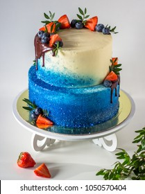 Two-tiered white and blue cake with fresh fruits and chocolate