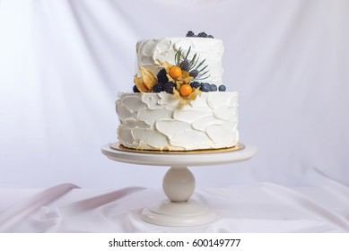 two-tiered white cream cake decorated with berries in a rustic style. trends for wedding desserts, foot design