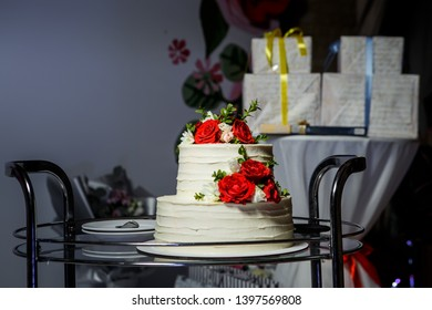 two-tiered white wedding cake decorated with red and pink roses served on glass tray against gift boxes