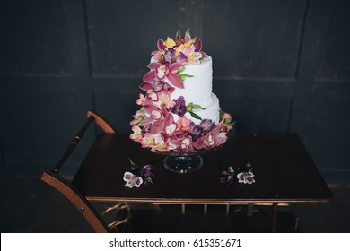 Two-tiered white wedding cake decorated with flowers and stands on a wooden table against background of black wall