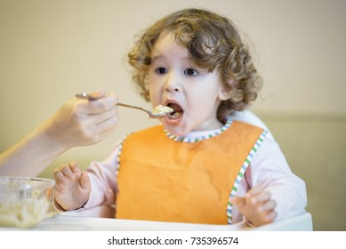 The two-year-old child eats porridge and looks TV. Little girl opens mouth to eat. Mother feeds her cute baby with a spoon. Adorable baby with bib sits on a highchair in the room.