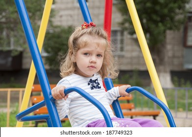 Two-year-old girl riding on a swing in the Playground. Portrait