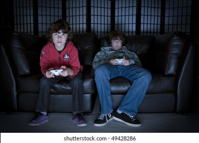Twp boys sitting on a couch playing video games