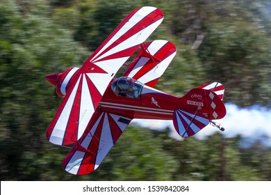 Tyabb, Australia - March 9, 2014: Pitts S-1T aerobatic biplane VH-EXO flying at low level during an aerobatics routine.