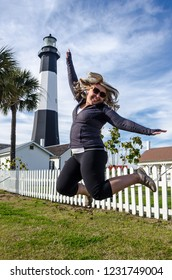 Tybee Island Light House in coastal Georgia. Blonde woman jumps in front of the lighthouse, concept for excitement, joy and fun